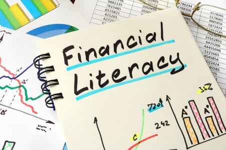 Littératie financière écrit sur une feuille de bloc-notes. concept de l'éducation.