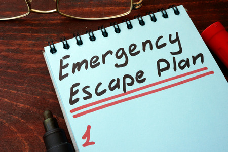 evacuate: Emergency Escape Plan written on a notepad with marker. Stock Photo