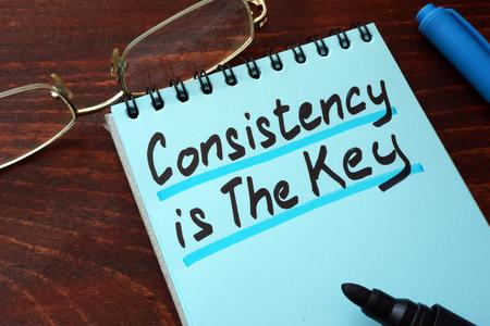 Consistentie is de sleutel geschreven op een notitieblok met een marker.