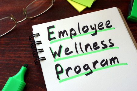 workplace wellness: Employee Wellness program written on a notepad with marker. Stock Photo