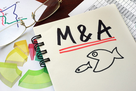 company merger: M&A Merger And Acquisitions written on a notepad with marker.
