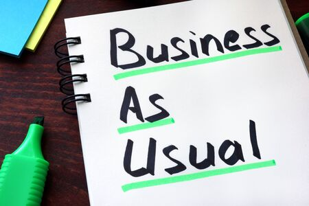 usual: Business As Usual written on a notepad with marker. Stock Photo