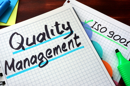 Key Performance Indicators KPI auf einem Notizblock mit Marker geschrieben. Qualitätsmanagementsystem QMS auf einem Notizblock mit Marker geschrieben. Standard-Bild