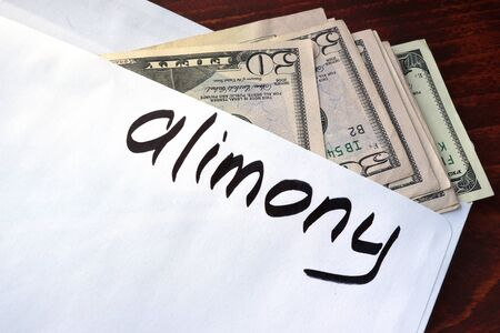 alimony: Alimony written on an envelope with dollars.