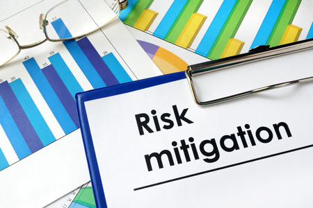 mitigating: Paper with words Risk mitigation and charts.