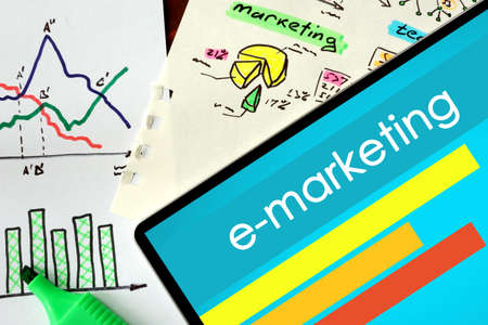 emarketing: Tablet with word e-marketing on a wooden background.