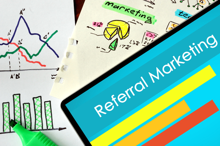 referral marketing: Tablet with words Referral Marketing on a wooden background. Stock Photo
