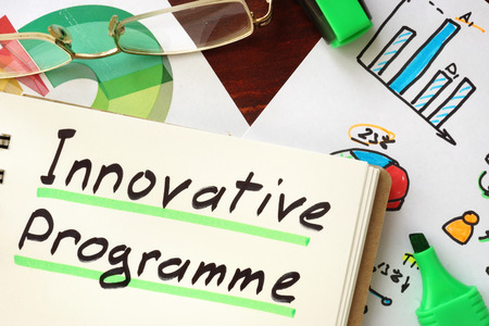 programme: Innovative programme sign written in a notepad. Stock Photo