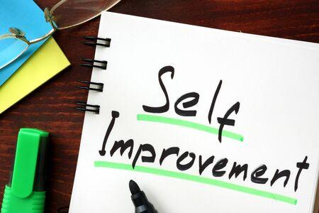 self improvement: Self improvement sign written in a notepad. Stock Photo