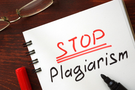copycat: Stop plagiarism sign written in a notepad. Stock Photo