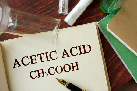 acetic acid: Word acetic acid written on a page. Chemistry concept.
