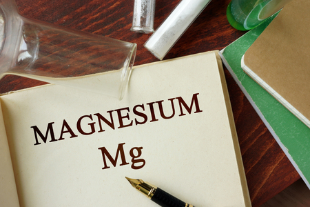 Magnesium written on a page. Chemistry concept. Imagens