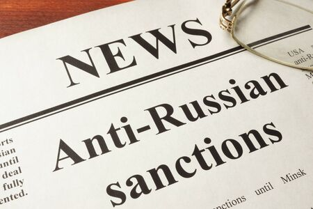 Newspaper with word news and Anti-Russian sanctions. Stock Photo