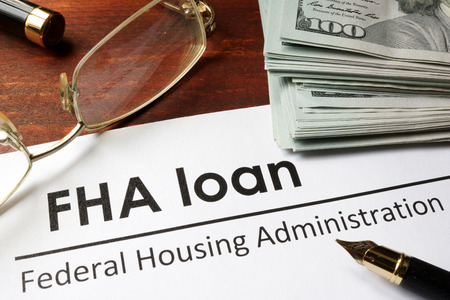viviendas: Papel con palabras de préstamo de la FHA en un fondo de madera.