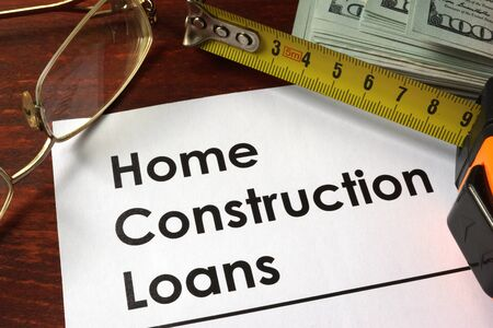 loans: Paper with words home construction loans on a wooden background.
