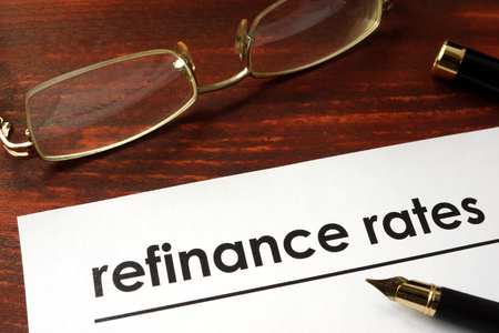 refinance: Paper with words refinance rates on a wooden background.