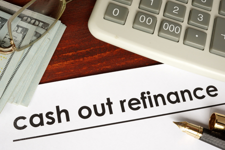 refinance: Paper with words cash out refinance on a wooden background.
