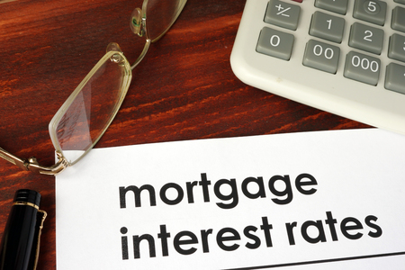 mortgage rates: Paper with words mortgage interest rates on a wooden background.