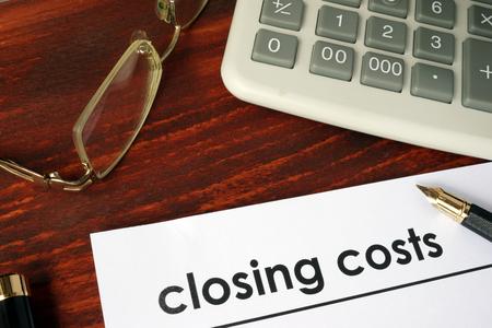 Papier met woorden afsluiting van de kosten op een houten achtergrond. Stockfoto
