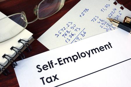 impuestos: Papel con palabras de impuestos por cuenta propia en un fondo de madera.