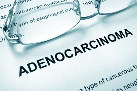 incontinence: Paper with word adenocarcinoma and glasses.
