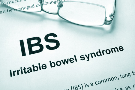 irritable bowel syndrome: Paper with words Irritable bowel syndrome (IBS) and glasses. Stock Photo