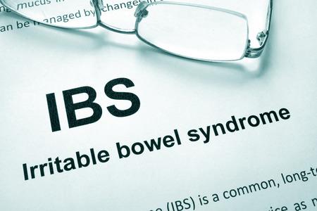 Papier met woorden prikkelbare darmsyndroom (IBS) en glazen.