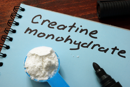 Notebook with  sign Creatine monohydrate and scoop with white powder. Stock Photo