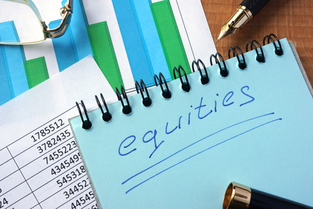 equities: Notepad with inscription  equities on a table. Stock Photo