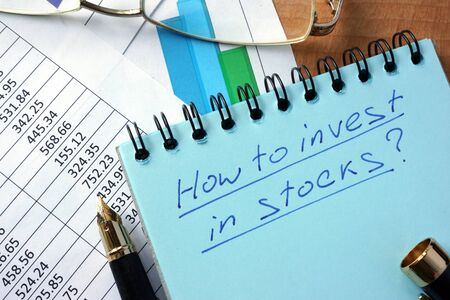invest: Notepad with inscription  how to invest in stocks on a table.