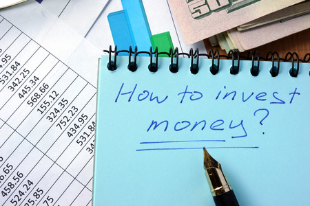 business funds: Notepad with inscription  how to invest money on a table.