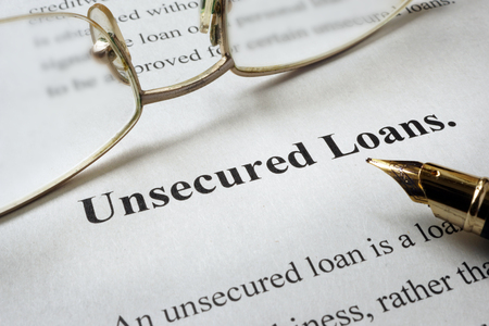 Page of book with words unsecured loans and glasses. Zdjęcie Seryjne - 60526911