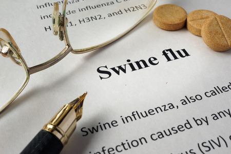 Page of book with diagnosis swine flu and glasses.