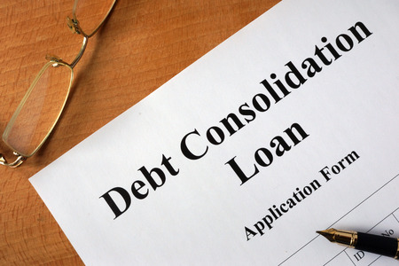 debt: Debt consolidation loan form on a wooden table. Stock Photo