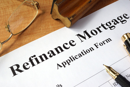 lender: Refinance mortgage form on a wooden table.