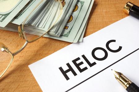 equidad: Página de papel con HELOC y dólares. Foto de archivo