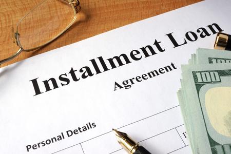 installment: Installment loan form on a wooden table.