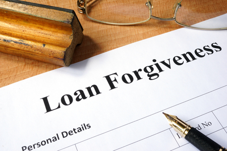 forgiven: Loan forgiveness form on a wooden table.