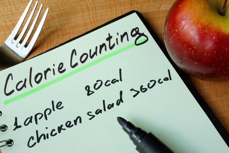 Agenda met een record calorieën tellen op een tafel. Stockfoto