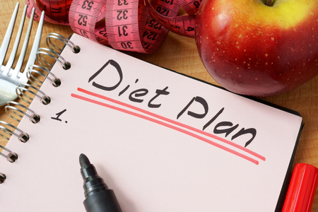 diet plan: Diary with a record diet plan on a table.
