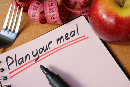 weight loss plan: Diary with a record plan your meal on a table. Stock Photo