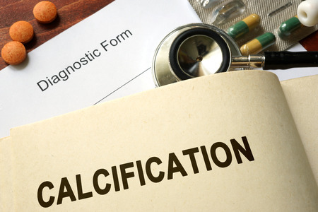 calcification: Page with word Calcification and glasses. Medical concept. Stock Photo