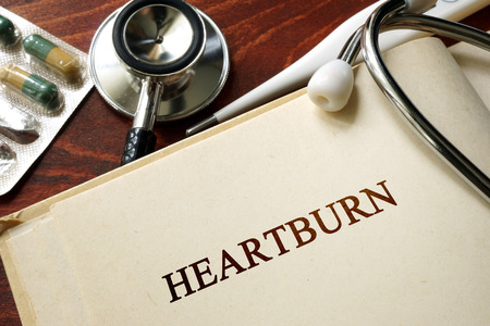 bloating: Page with word heartburn and glasses. Medical concept.