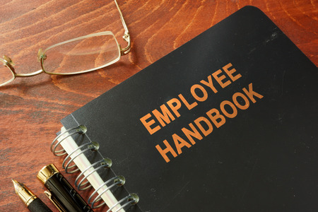Employee handbook on a wooden table and glasses.