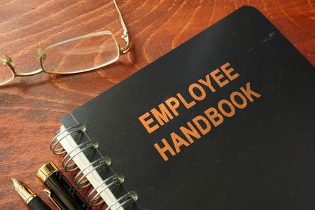 Podręcznik pracownika na drewnianym stole i okulary. Zdjęcie Seryjne