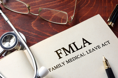 leave: Page with FMLA family medical leave act on a table.