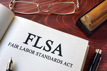 Page with FLSA fair labor standards act on a table. Standard-Bild