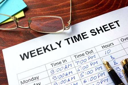 Paper with weekly time sheet on a table.