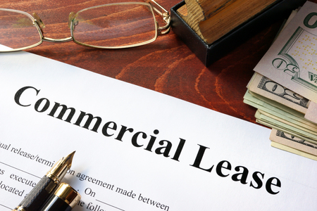 anuncio publicitario: Contrato de arrendamiento comercial con el dinero sobre la mesa. Foto de archivo