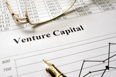 venture: Sign venture capital on a paper and glasses. Stock Photo